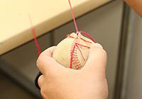 写真:傷んだ硬式野球ボールを糸で縫っている様子