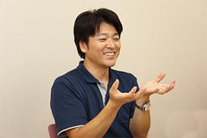 写真:百合川施設長がジェスチャーを交えて笑顔で話してる様子
