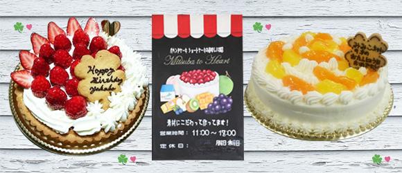 画像:左からいちごのホールケーキ、お店の営業時間や定休日がかかれたボード、かんきつ類のホールケーキ