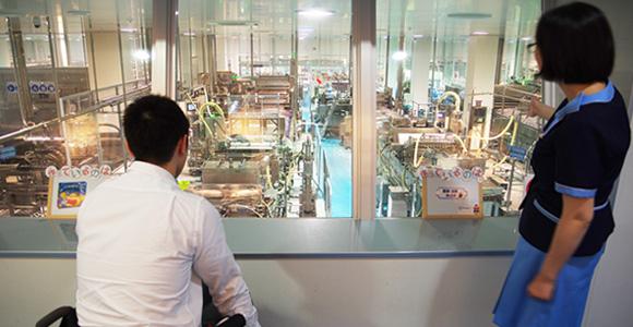 写真:ガイドの方から工場の生産ラインの説明を受けている編集部員の様子。